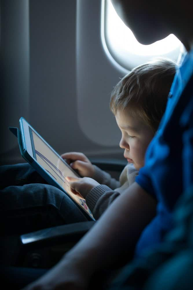 Boy playing on tablet on an airplane