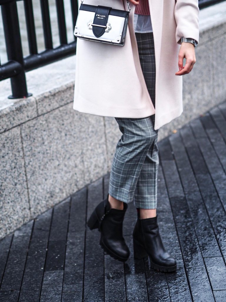 A woman with a Prada bag and leather boots