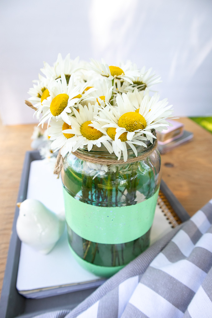 A mason jar filled with daisies and painted with teal glitter paint