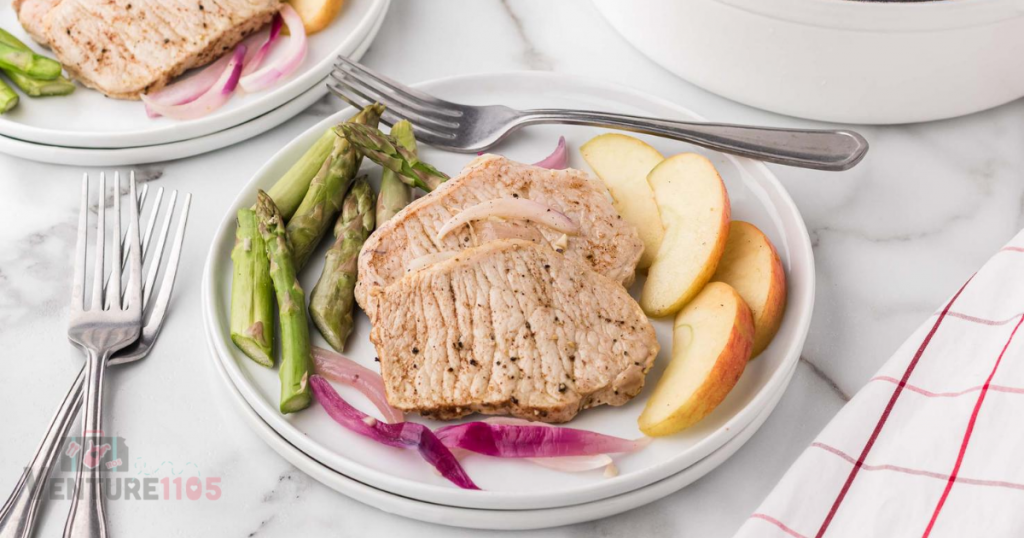 A plate with pork, apples, and asparagus