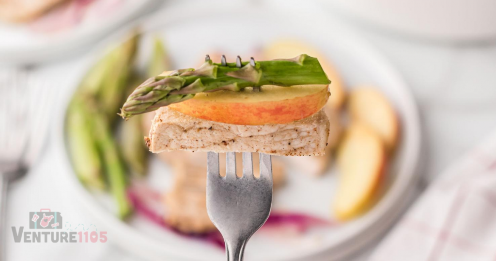 A fork with asparagus, apples, and pork on it
