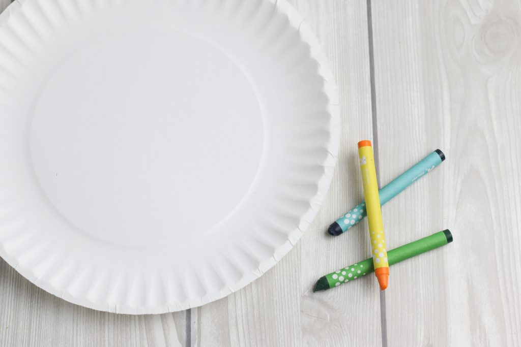 A white paper plate and 3 crayons