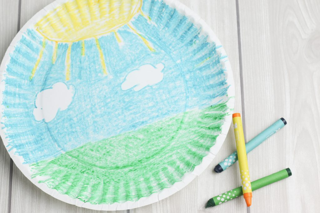 A paper plate with green grass and a blue sky drawn on it, next to 3 crayons