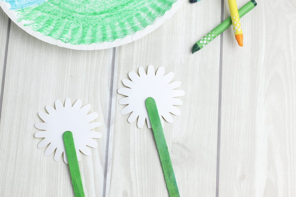 gluing green craft sticks to paper flower shapes