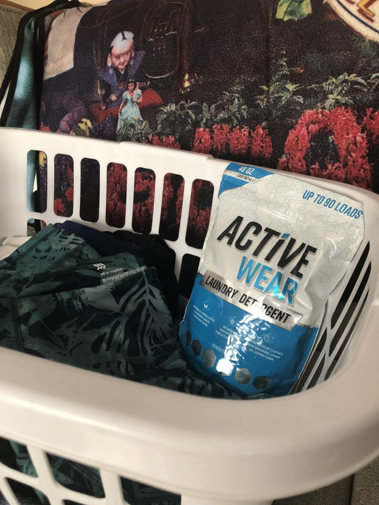 A bag of Active Wear Detergent in a laundry basket