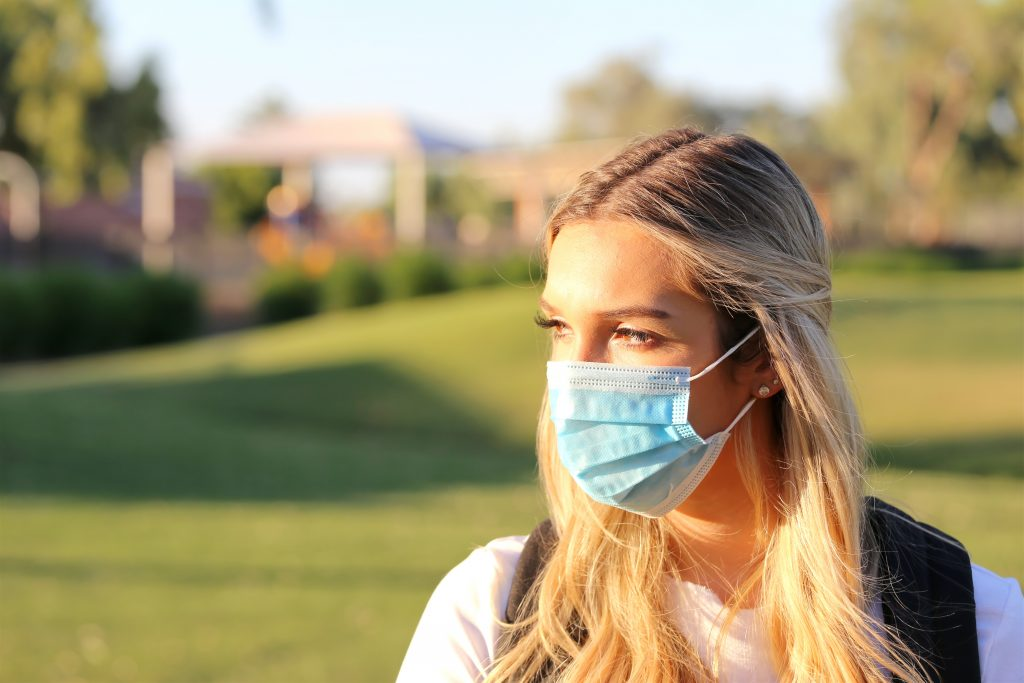 A blonde woman wearing a face mask
